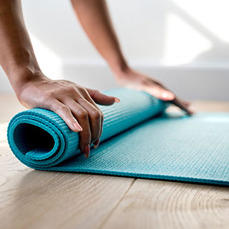 person rolling yoga mat